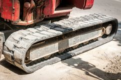 Front part of small earth mover bulldozer excavator with tracks on the street construction site prepared for work.  royalty free stock photography