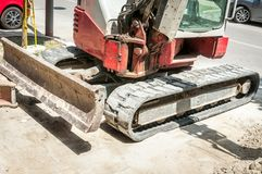 Front part of small earth mover bulldozer excavator with tracks on the street construction site prepared for work.  stock images