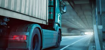 Front part of a truck driving through a tunnel. Front part of a green truck carrying a container. It`s driving on a highway through a tunnel towards the exit royalty free stock images