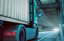Front part of a truck driving through a tunnel. Front part of a green truck carrying a container. It`s driving on a highway through a tunnel towards the exit stock photo