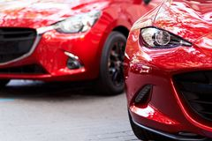 Front part of two red cars. Front part of two new red modern cars on the street royalty free stock images