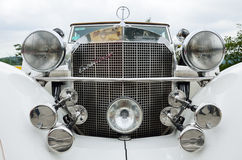 Front part of the vintage car Excalibur. The hood with many headlights of the old-fashioned white automobile Excalibur Stock Photo
