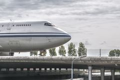 Front of a plane driving over a runway bridge stock images