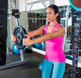 Front plate raise brunette girl workout at gym Stock Photos