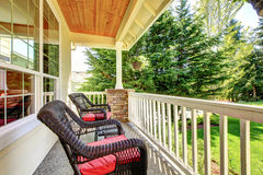 Front porch with brown chairs and red cushions. Royalty Free Stock Photography
