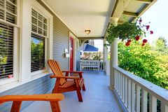 Front porch of the grey house with white railings and two windows. Royalty Free Stock Photography