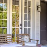 Front porch of a home with chairs and glass window. View of the front of a home with gray front door and reflective glass windows. Wooden chairs with cushions royalty free stock image