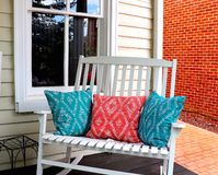 Front Porch Rocker and Pillows. Front porch of this home has a white double rocker chair with decorative throw pillows. Outdoor furniture rustic decor brick tile stock photos