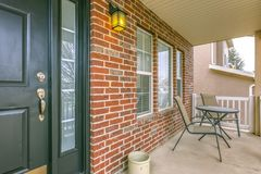 Front porch of a home with table and chairs in front of brick wall and window. The outdoor scenery is reflected on the sidelight that flanks the green front stock images