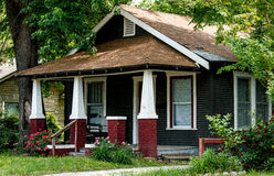 Front Porch with a Missing Tooth. Closeup shot of the front of an old house in a residential neighborhood with large trees, flowers and other plants, and fairly Royalty Free Stock Photography