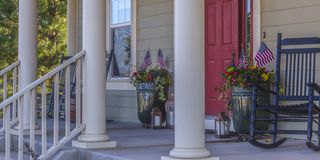 Front porch with stairs red door and rocking chair. Stairs leading to the front porch framed by white columns and with a red door. Rocking chairs, potted stock photo