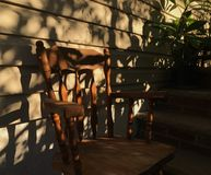 Front Porch Sun and Shadow Silhouette of Chair and Plants royalty free stock photography