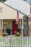 Modest home proudly displaying American flag and hanging flower stock photos