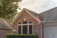 Facade of American home proudly displaying flag. Front porch of typical one story house proudly displaying American flag Stock Photo