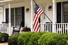 Front Porch. Of white colonial home with american flag and rockers Stock Image
