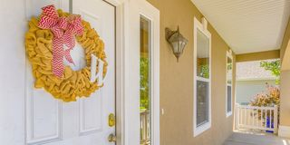 Front porch and white door with yellow wreath. View of a house with a porch and reflective glass windows on a sunny day. A yellow ruffled wreath with red stock photo