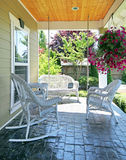 Front porch with white furniture and flowers. Front porch with white outdoor furniture and flowers Stock Photo