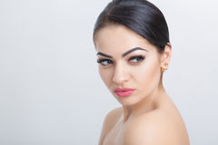 Front portrait of attractive young brunette woman on grey background closeup. girl with clean skin Stock Photos