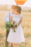 The front portrait of the groom hugging the bride back. The couple is dressed in the vintage style. Royalty Free Stock Image
