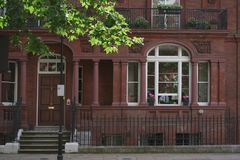 Front house with windows in London. Front red brick building in London. Entrance door. Man seen through window Royalty Free Stock Photo