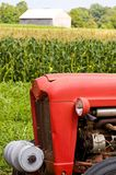 Front of red farm tractor. A view of the front of an old red farm tractor on the edge of a cornfield with a wooden barn in the distance stock images