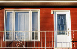 Front of red house. Home: front of new house with red cedar wood siding,white door and window trim Royalty Free Stock Photo