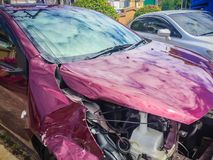 Front of red new car distorted by accident. Crashed new red car Royalty Free Stock Photos