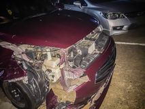 Front of red new car distorted by accident at night. Crashed new Stock Image