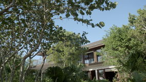 The front of a relaxing resort villa. Tilting down shot of a relaxing resort villa built mostly from wood, with lush green plants and flowers in the front garden stock footage