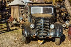Front Of Retro Truck In Salvage Yard. Front Of Vintage Truck In Salvage Yard With Chicken Underneath Royalty Free Stock Image
