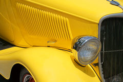 Front right yellow antique car. Showing radiator and headlamp stock photos
