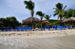 Front row beach seating. Palm Trees, Blue Beach chairs, palm leaves covered sun hut makes up the ambience of the white sand beach found in the island of Palomino Royalty Free Stock Photo