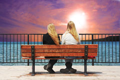 Front Row Seat. High definition image of two young ladies sitting on bench at the edge of a lake watching a colorful sunset Stock Photography