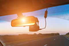 Front seat view of road, rear view mirror and speed recorder in sunlight royalty free stock image