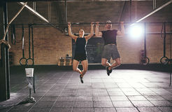 Front shot of two sportsmen doing pull-ups Royalty Free Stock Photo