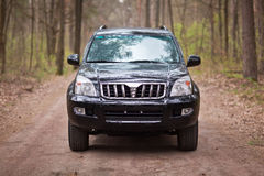 Front side of the black SUV in forest.  Royalty Free Stock Photos
