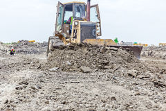 Front side of heavy earthmover construction machine in action. Front view on bulldozer while he moving, leveling ground at building site Stock Photos