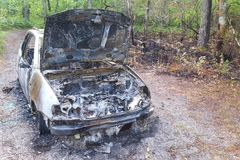Side view of abandoned burned out car left on side of the road with hood left open expose burned engines. Front and side view of abandoned burned out car left on Royalty Free Stock Photos