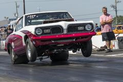 Drag racing. Front side view of Plymouth barracuda drag car making a wheelie Royalty Free Stock Photography
