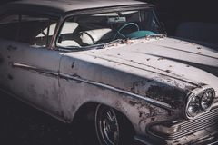 Front side view of a worn and beat up classic American car from the fifties. Partial close up of an old untouched and not restored classic car from 1958 stock photography