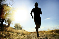 Front silhouette young sport man running cross country workout at summer sunset Royalty Free Stock Photos