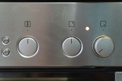 The front silver control panel of the stove with handles switching royalty free stock photography