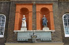 Bluecoat scholar statues in Wapping, London,UK. The front of St John of Wapping school in London, founded in 1695 with a statue of a girl and one of a boy pupil Stock Image
