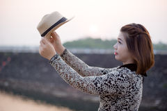 The front of sunset. Woman looking her hat with sunset behind Royalty Free Stock Photo