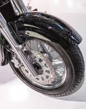 The front tire of a parked custom motorcycle Stock Photos