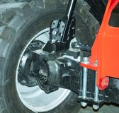 Front Tractor Suspension. Fastening of a wheel to a forward beam of a tractor stock photo