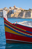 The front of traditional maltese boat with the view of Senglea p. The front of the traditional maltese boat Luzzu entering the frame with the view of Senglea (L Royalty Free Stock Photo