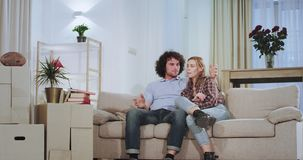 In front of the tv on the sofa charismatic couple enjoying the time in a new house apartment they happy standing up from. The sofa and going out from the camera stock video footage