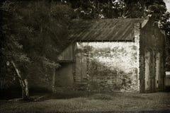 Front und Seite des alten Backsteinbaus mit Metalldach lizenzfreie stockfotos