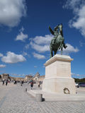 In front of Versailles & King Louie XIV Statue. In front of Chateau de Versailles & King Louie XIV Statue Against Blue Sky Stock Photography